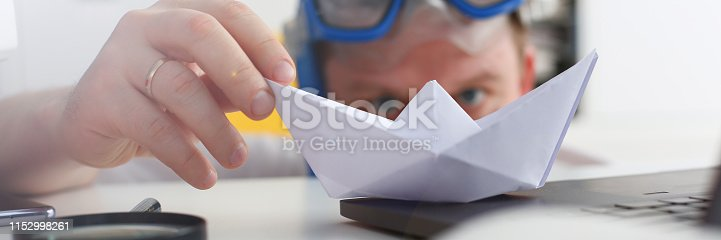 Man wearing suit and tie in goggles and snorkel play with paper ship in office closeup. Count days to leave annual day off workaholic freedom fun tourism resort idea ticket sale concept
