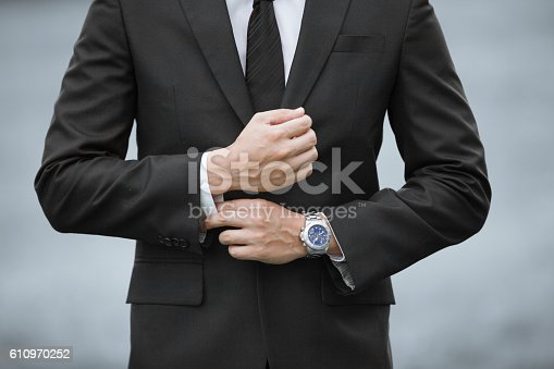 516141885istockphoto Man wearing suit and watch 610970252
