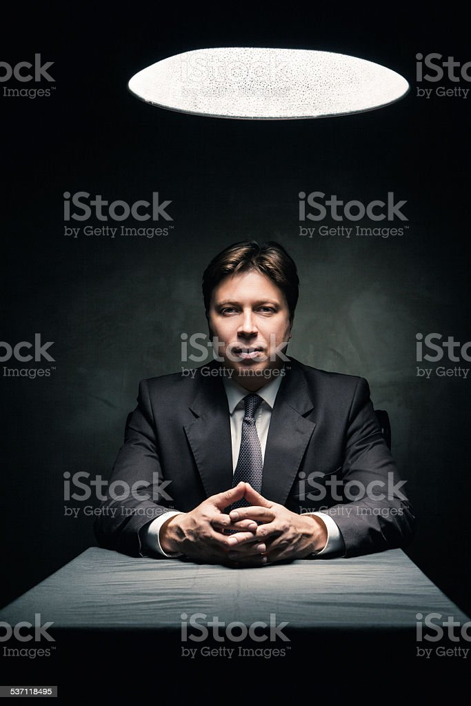 Man wearing suit in dark room illuminated by lamp stock photo