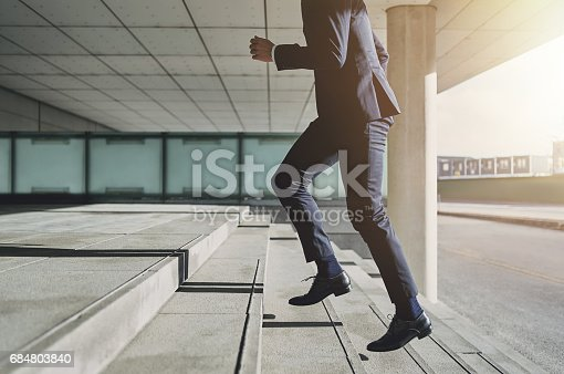 istock Man wearing suit runs up the stairs 684803840