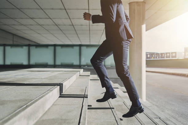 Man wearing suit runs up the stairs stock photo