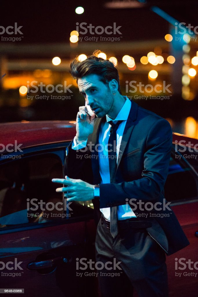 man wearing suit talking on his smartphone at night royalty-free stock photo