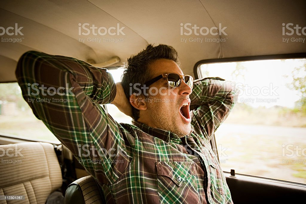 Man wearing sunglasses and yawning in car stock photo