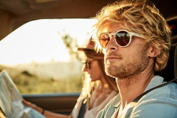 Mann trägt Sonnenbrille von Frau im Auto – Foto