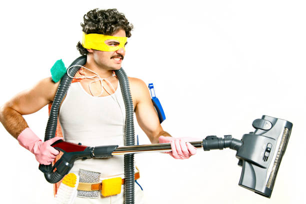 Man Wearing Superhero Mask Holding Vacuum and Cleaning Supplies stock photo