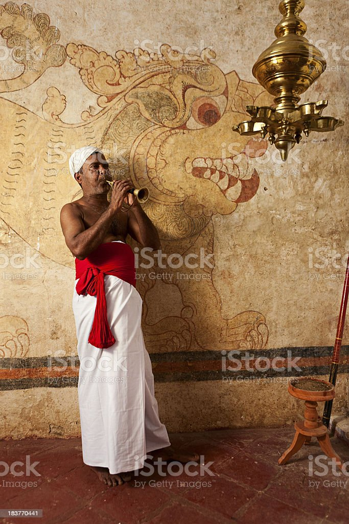 Man wearing  traditional Sri Lankan costume playing trumpet inside temple. royalty-free stock photo