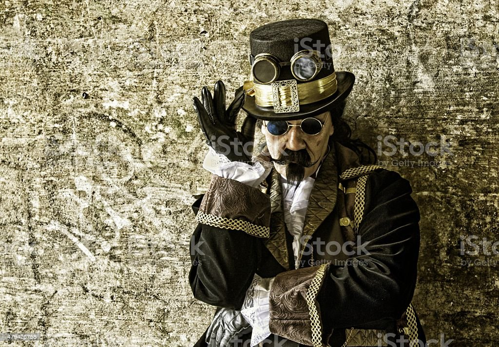 Man wearing victorian/steampunk clothing against gold background stock photo