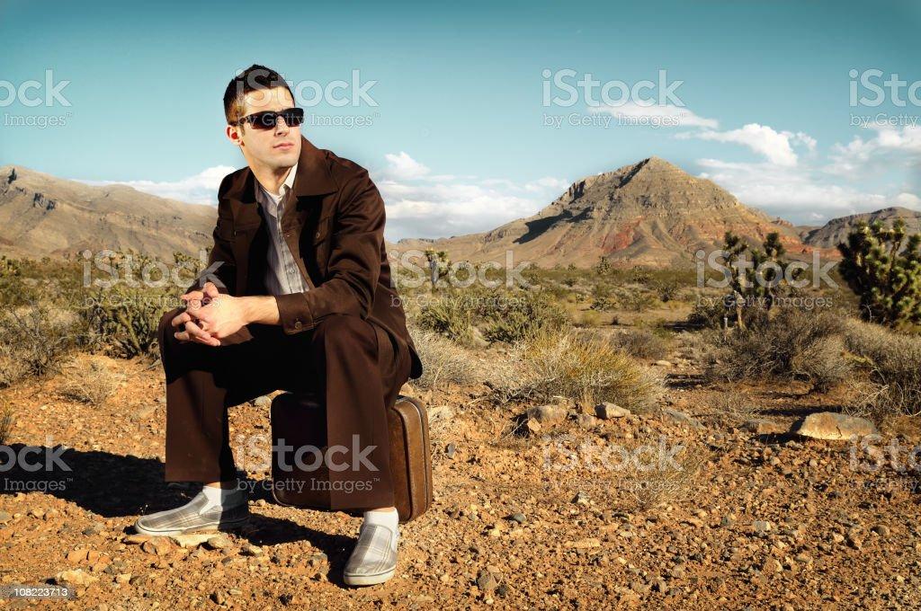 Man Wearing Vintage Suit Sitting in Desert royalty-free stock photo
