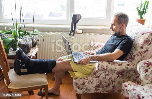 Man wearing walking boot for achilles tendon treatment is using laptop at home