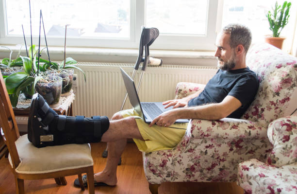 man wearing walking boot for achilles tendon treatment is using laptop at home. injured man with crutches. - broken leg stock photos and pictures