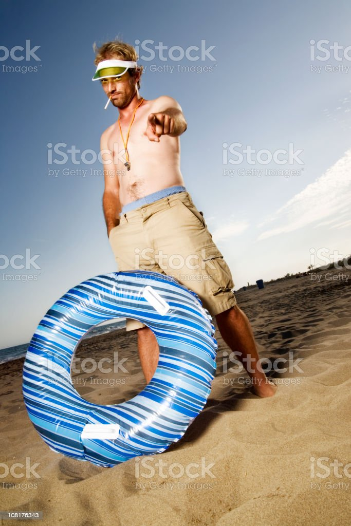 Man Wearing Whistle Smoking and Pointing on Beach royalty-free stock photo
