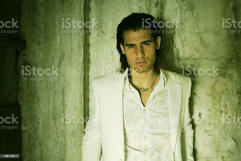 Man Wearing White Jacket and Shirt Leaning Against Grunge Wall royalty-free stock photo