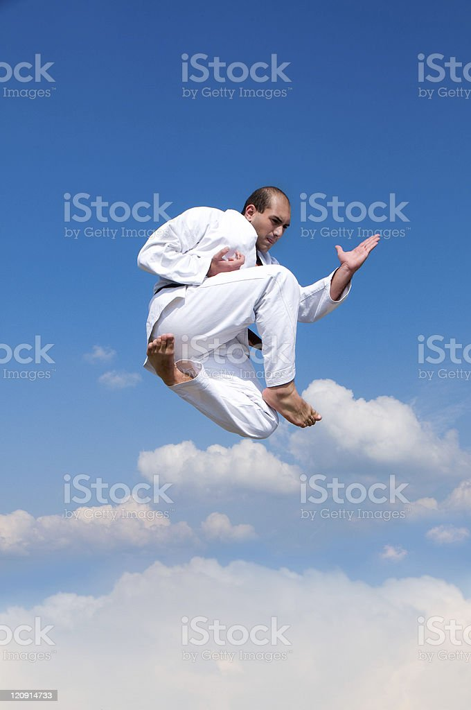 Man Wearing White Karate Suit and Jumping stock photo