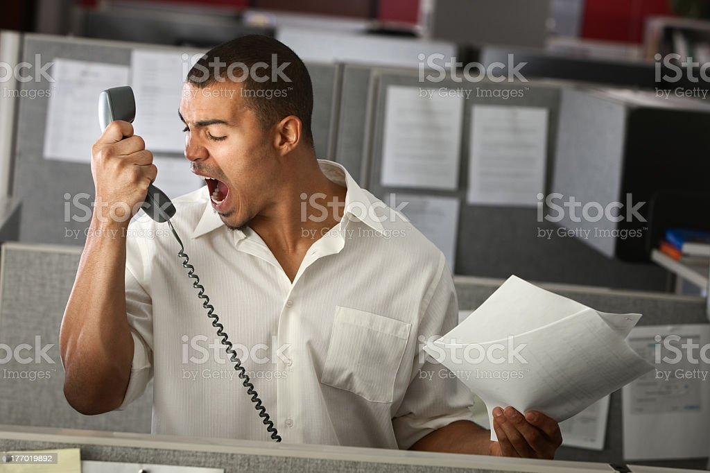 Man wearing white shirt shouting into phone in an office royalty-free stock photo