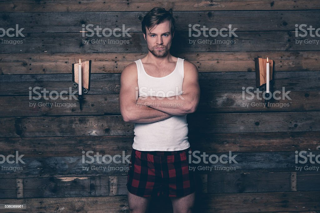 Man wearing white singlet shirt and red flannel shorts. stock photo