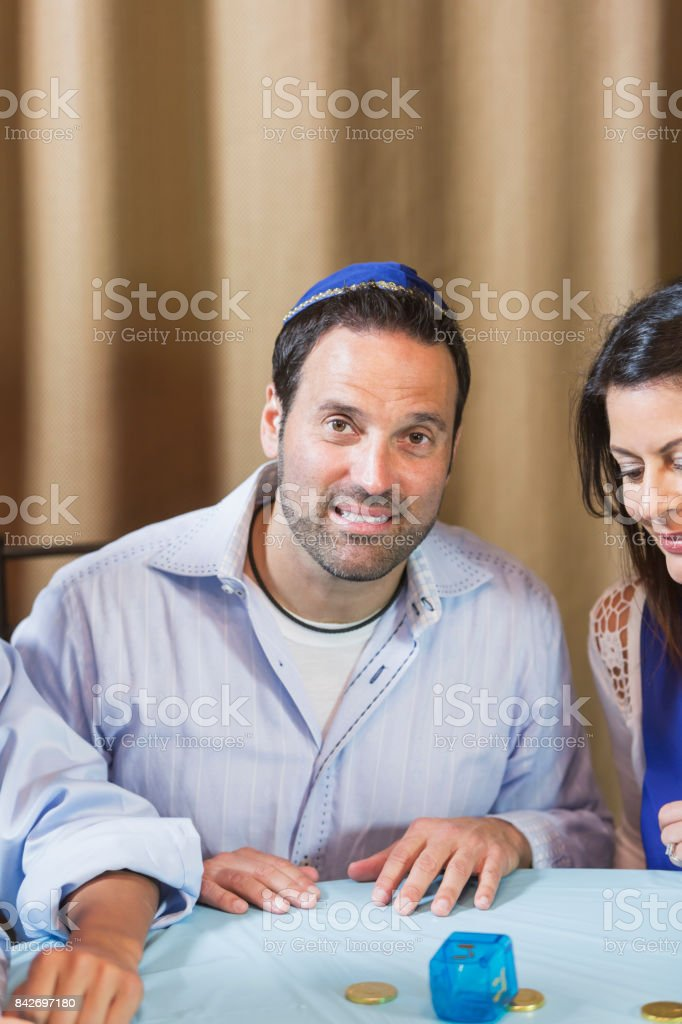 Man wearing yarmulke playing dreidel stock photo