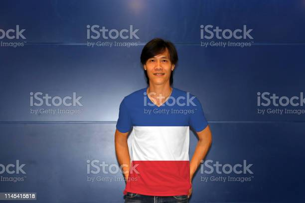 """Man wearing Yugoslavia (1918""""u20131941) flag on shirt and standing on the blue wall background."""