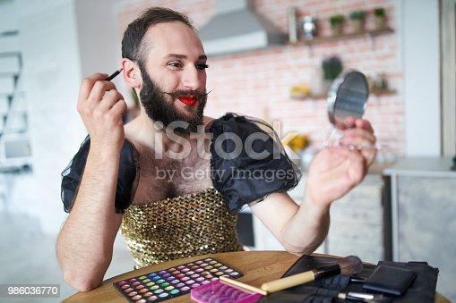 Man wears a dress and applying make-up