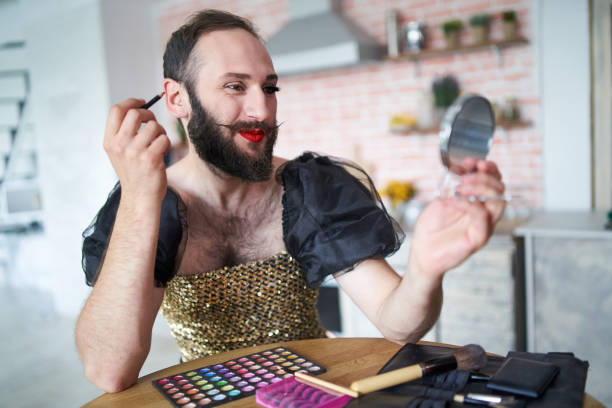 man wears a dress and applying make-up - transvestite stock photos and pictures