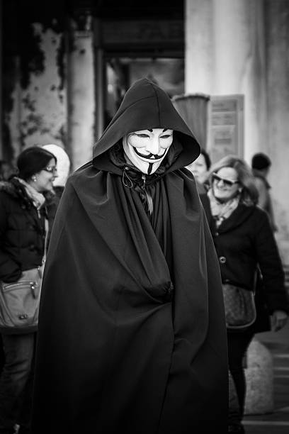 man wears a v for vendetta, guy fawkes mask - guy fawkes mask stock photos and pictures