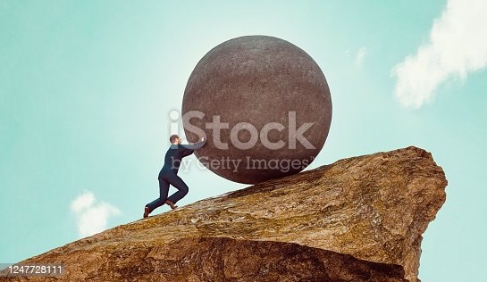 Concept of business work. Man stands on a hill and uses his strength to push a big rock up the steep hill side. Pushing a rock up hill is also a reference to the greek mythology Sisyphus ot Sisyphos. Note: The man is a 3D-render with face scan. Model release attached.