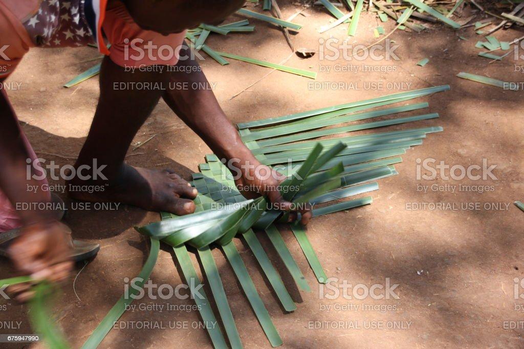 Man weaving a basket with plant leaves, Kiwengwa Beach, Zanzibar, Indian Ocean, Africa stock photo