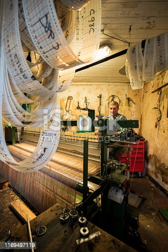 A male crofter busy at work on his foot powered loom at home weaves wool sheared, dyed and spun on the island according to Parliment bylaws to create distinctive Harris tweed fabric on the Isle of Lewis, framed by loops of patterns used in creating various designs, Outer Hebrides, Scotland, UK