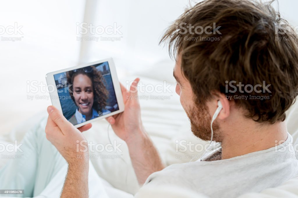 Man web chatting on a tablet with a friend traveling stock photo