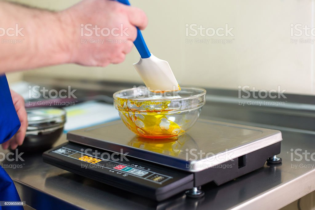 Man weighs caramel in a glass bowl - foto de stock