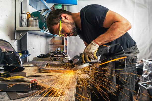 hombre de la autógena en un procesos de un metal con una amoladora - foto de stock