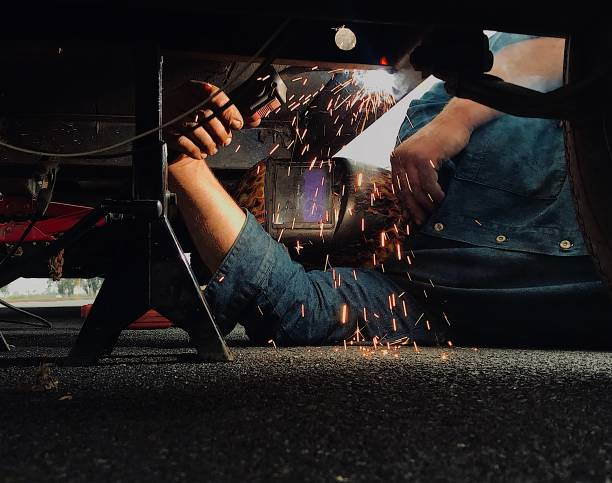 Man welding his trailer frame. Man welding his trailer frame after his trailer broke while driving vehicle trailer stock pictures, royalty-free photos & images