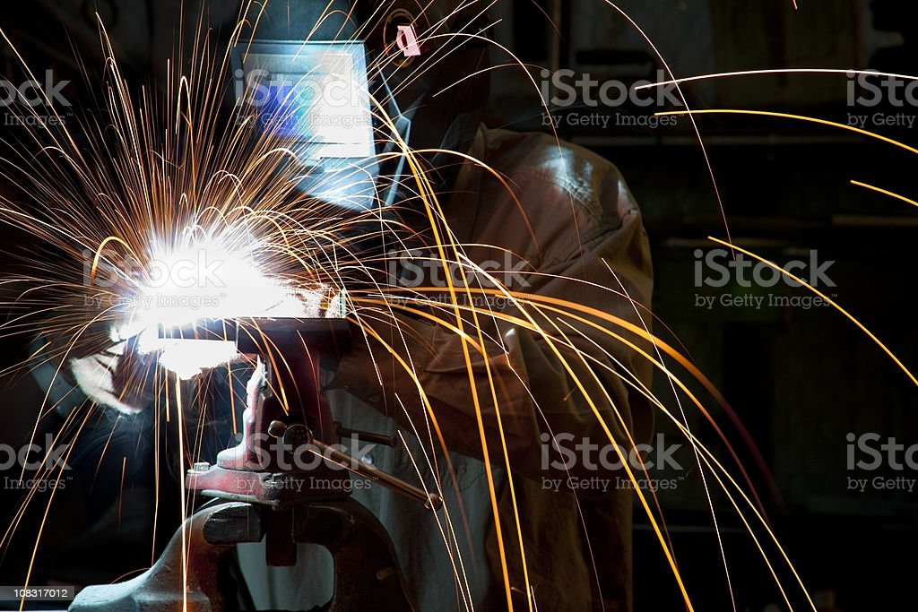 Man welding in workshop sparks flying, motion royalty-free stock photo