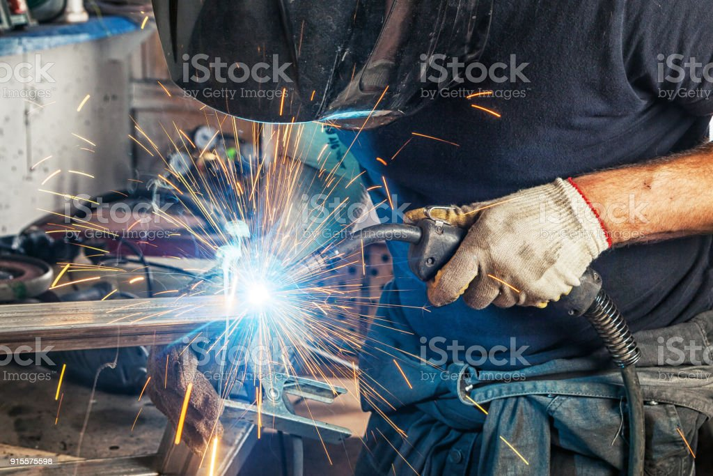 man welds with a welding machine metal stock photo