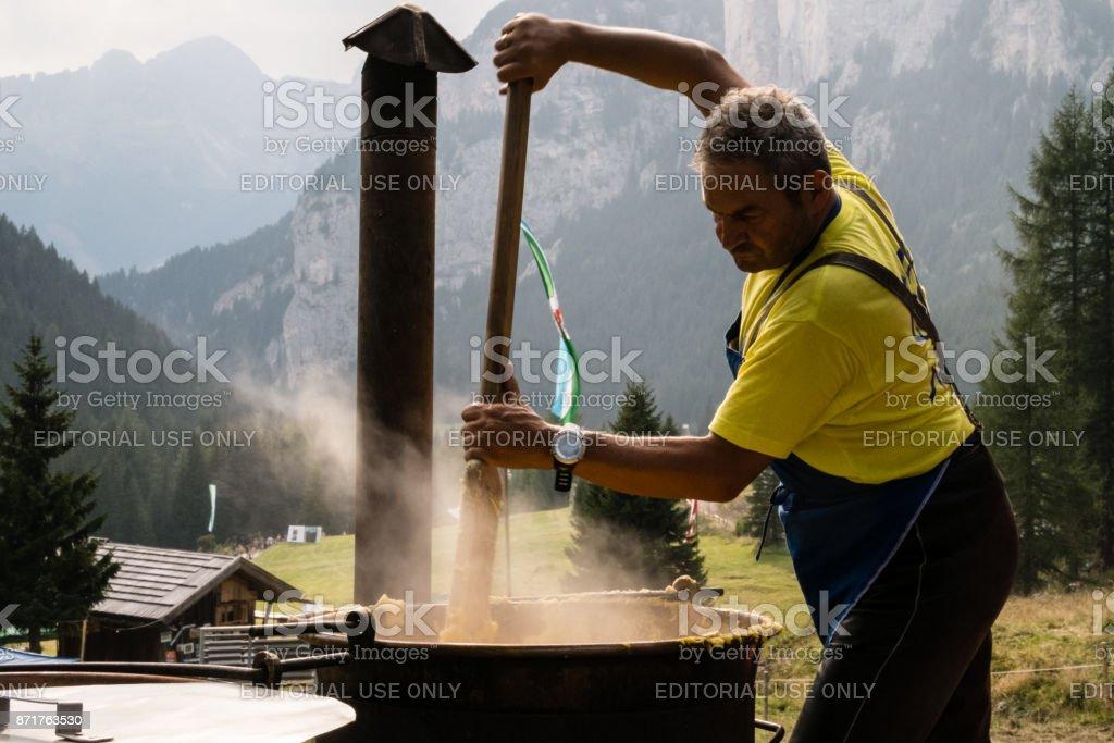 Man while mixing polenta at Festa Ta Mont, traditional Ladino festival stock photo