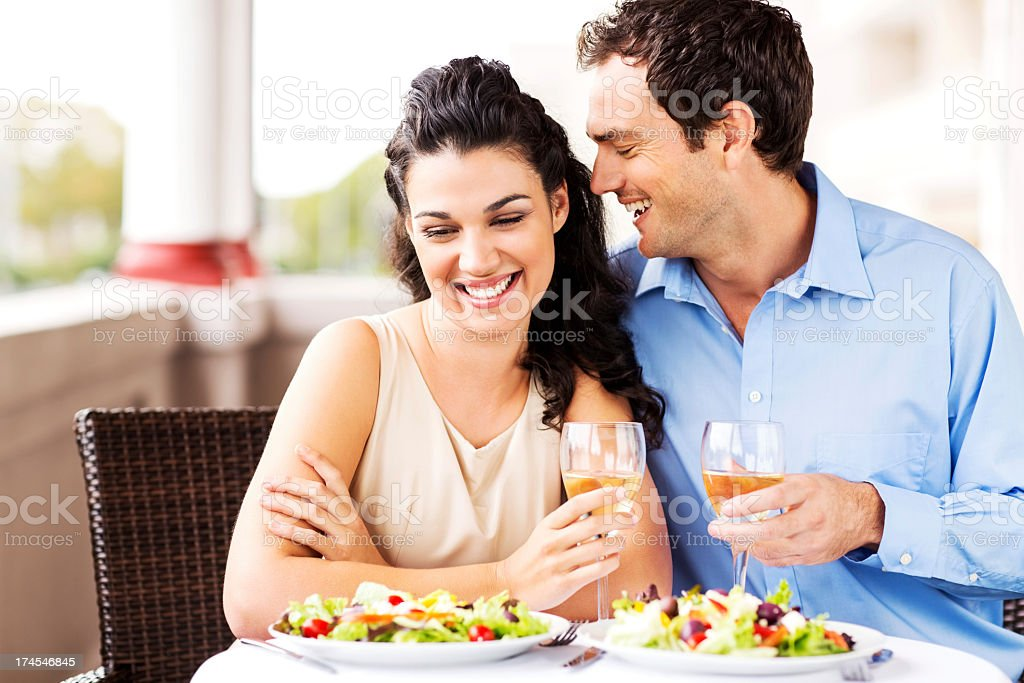Man Whispering in Girlfriends Ear On Romantic Date royalty-free stock photo