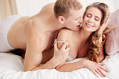 istock Man whispering in woman's ear 694408362