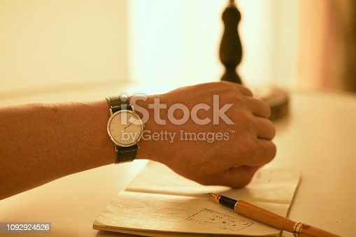 Wrist watch on the arm.Pen and passport on the desk