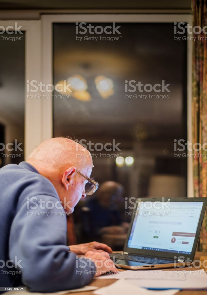 Old man of 93 years having trouble using his computer to check his...