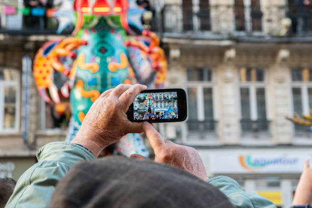 Man who makes videos and photos with a mobile phone on the great carnival parade Eldorado Lille 3000. Lille,FRANCE-May 04,2019: Man who makes videos and photos with a mobile phone on the great carnival parade Eldorado Lille 3000.Lille 3000 is an association representing a cultural program. hauts de france stock pictures, royalty-free photos & images