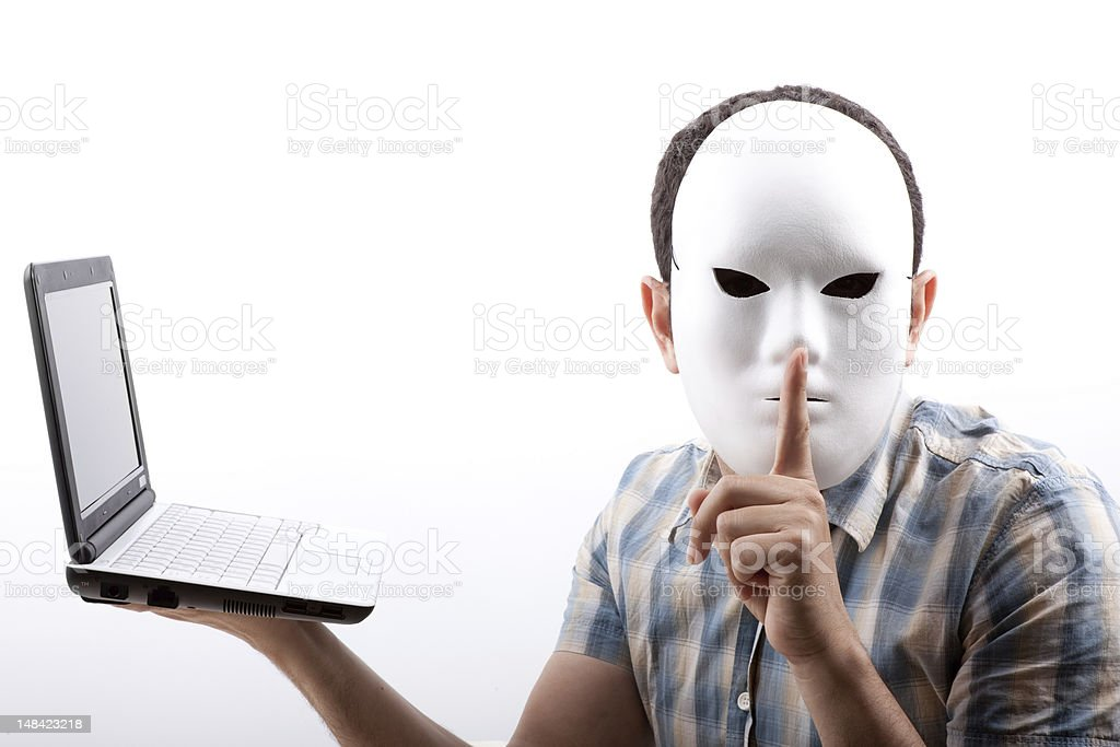 Man Whose Face Obscured With Mask Holding Computer And Warning stock photo