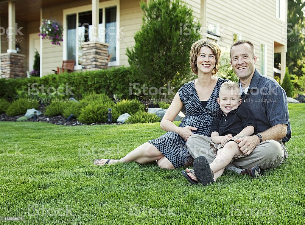 Man, wife and child outside of family house stock photo