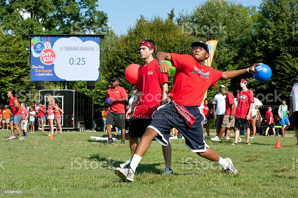 Man Winds Up To Throw In Outdoor Dodge Ball Game stock photo