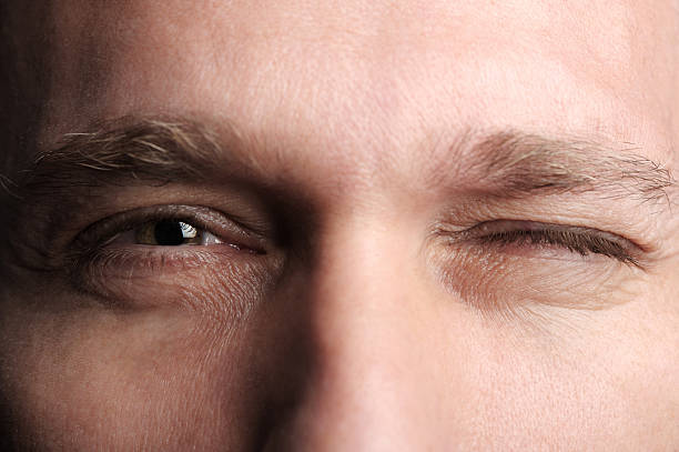 Man Winking Extreme Close up close up of a man winking, Focus on Eyes blinking stock pictures, royalty-free photos & images