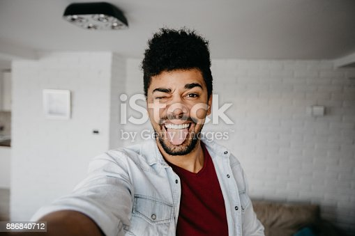 istock Man winking to a camera and taking a selfie 886840712