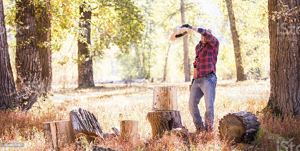 Man wipes sweat from brow while resting from chopping wood stock photo