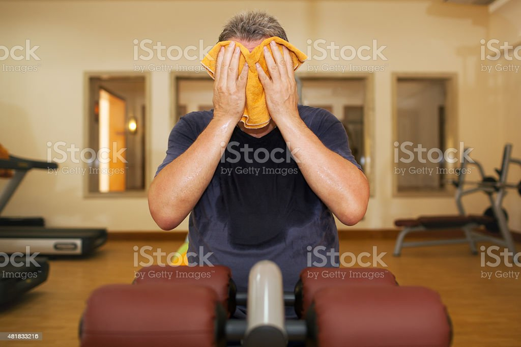 Man wiping face with a towel after training stock photo