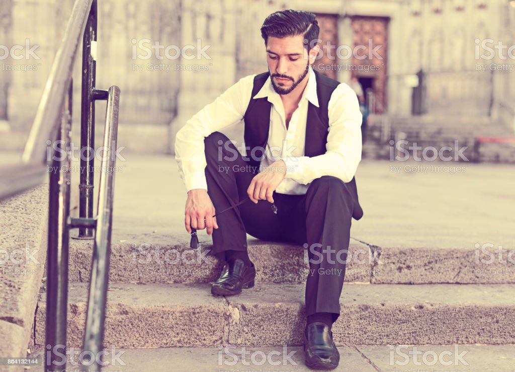 Man wistfully sitting on stone stairs royalty-free stock photo