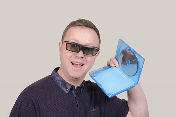 man with 3d glasses and 3d blu-ray disc - blu ray disc photos et images de collection