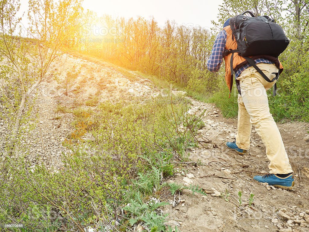 man with a backpack walk uphill the forest trail . stock photo
