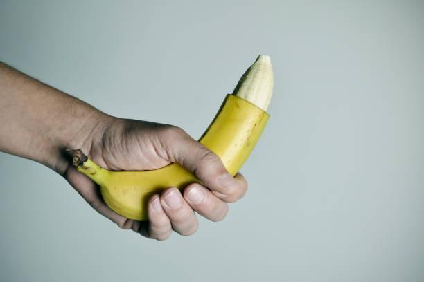 homme avec une banane avec le bout de sa peau retirée - circoncision photos et images de collection